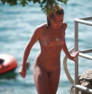 Nackte Teen steht auf dem Strand.